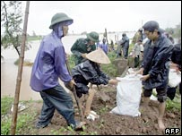 People build up a portion of a dyke in northern province of Nam Dinh on 27 September 2005