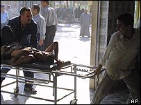 A wounded man is rushed to hospital in Baquba after a bombing, 27 September 2005