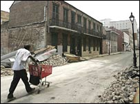 A man pushes a shopping cart through the damaged French Quarter