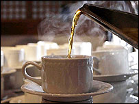 Cup of tea being poured from a steel kettle