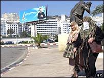 Algerian women walk near a campaign poster of Algerian President Abdelaziz Bouteflika