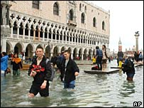 Tourists and residents wade through a flooded St Mark's Square in Venice