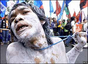 A protester mimics a scene of poverty while others shout anti-government slogans during a demonstration near the Presidential Palace in Jakarta, 29 September 2005.