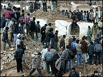 Crowd gathers around destroyed homes in village of Dahuyeh, Iran
