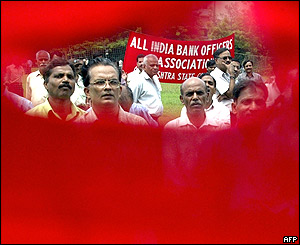 Striking bank employees are pictured through a torn banner