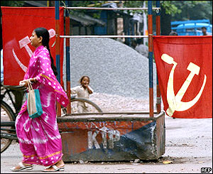 A woman walking in front of communist flags