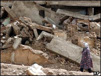 Woman walks in front of an earthquake-damaged house in Reyhanshahr on the outskirts of Zarand, Iran