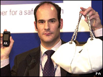 DCI Cundy holds up a white Prada bag and mobile phone similar to those taken from Miss Bowman