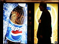 Man walking past a Pepsi vending machine