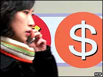 A South Korean woman walks past a dollar sign at a Seoul bank