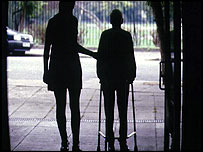Elderly pensioner with walking frame, aided by carer