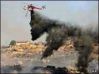 A helicopter drops fire retardant near Los Angeles