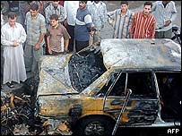Iraqis gather at the site of one of three car bombings in Balad on Thursday night that has killed at least 95