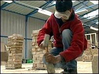student chiselling brick