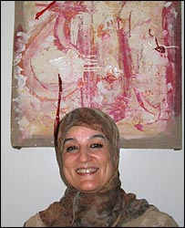 Nadia Yassine stands in front her modernist painting of Allah's name