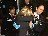 A police officer leads a woman from Cuddles