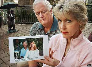 Terri Knill and her husband Roy Maguire with a picture of tsunami victims John and wife Jackie Knill