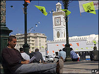 Algerian men relax on the Place des Martyrs by the Algiers Great Mosque