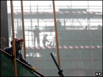 A Chinese worker looks out from scaffoldings at a construction site in Beijing