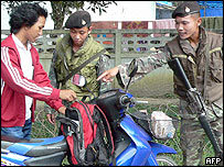 Thai security officers check the bag of a civilian in Ranga district, southern Narathiwat province, 24 February 2005.