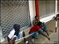 Togolese sitting outside a closed Lome business
