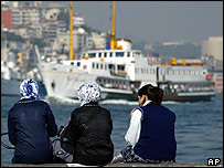 Turkish girls sit on the banks of the Bosporus, Istanbul