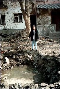 Civilian in front of her bomb-shattered house in Grozny