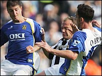 Alan Shearer is tackled by the Portsmouth defence