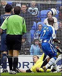 Henri Camara flicks the ball over Jussi Jaaskelainen