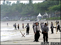 Police stand on the beach in front of a cafe where one of the blasts took place