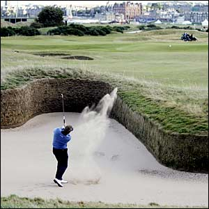 Colin Montgomerie plays out of a bunker on the 14th