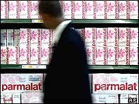 Man passing shelves containing Parmalat long-life milk