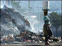 A Haitian woman walks past a pile of burning garbage used by gangs to block the roads in the shantytown of Belair,  Port-au-Prince