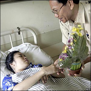 Indonesian-Chinese bomb blast victim Ifen Sani, a 27-year-old accountant, receives a bouquet of flowers from a local government official at Sanglah Hospital in Denpasar
