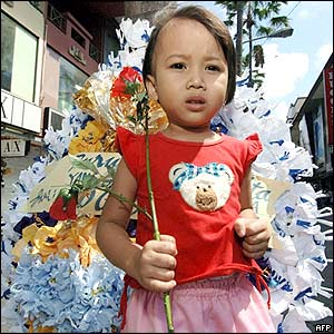 An Indonesian girl carries paper-made flowers to one of the bomb blast sites in Kuta