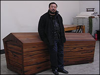 Ai Weiwei standing next to 'guancai', the Chinese word for coffin