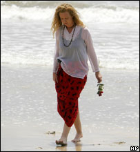 A woman walks back from the ocean after throwing flowers in the water at the site of two bomb explosions on Jimbaran Beach, Bali, Indonesia Monday Oct. 3, 2005.