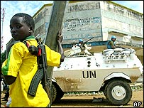 A child fighter of the rebel Union of Congolese Patriots stands near a UN armoured personnel carrier in Bunia, DR Congo (file photo, 30 May 2003)