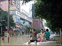 Residents make their way along a flooded street in Fuzhou, China's Fujian province 03 October 2005.