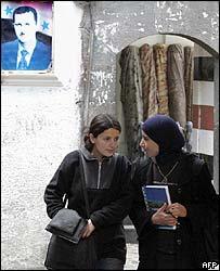Women walk past a poster of Bashar al-Assad in Damascus
