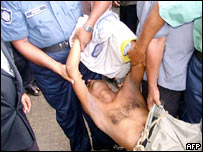 Police officals carry a suspect following a bomb blast in Chittagong