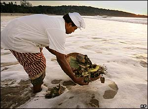 A Balinese man makes an offering to the sea on Jimbaran Beach, Bali