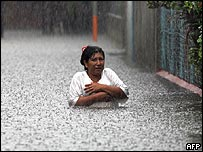 Woman wades through her street in San Jose, Guatemala