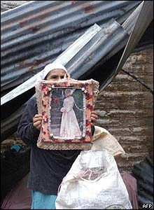 A woman shows the portrait of her daughter killed in Lourdes Colon, El Salvador