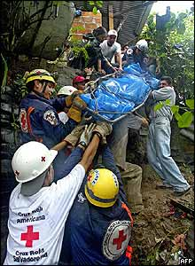 Rescue workers carry the body of one of the members of a family killed in 12 de Abril community