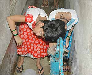 Conjoined Indian twins, Saba, left and Farah washing up at home in Patna (Picture by Prashant Ravi)
