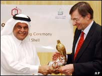 Qatar's petroleum minister, Abdallah bin Hamad Al-Attiyah, and Shell chief executive Jeroen van der Veer exchanging gifts after signing the deal
