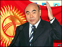 Kyrgyz President Askar Akayev gestures answering a question as he stands in front of national flag at a polling station in the Kyrgyz capital Bishkek Sunday, Feb. 27, 2005.