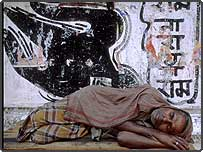 Homeless man asleep on pavement, with political graffiti on wall in Calcutta, India