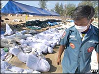 Rescue worker with bodies in Thailand after the 2004 tsunami